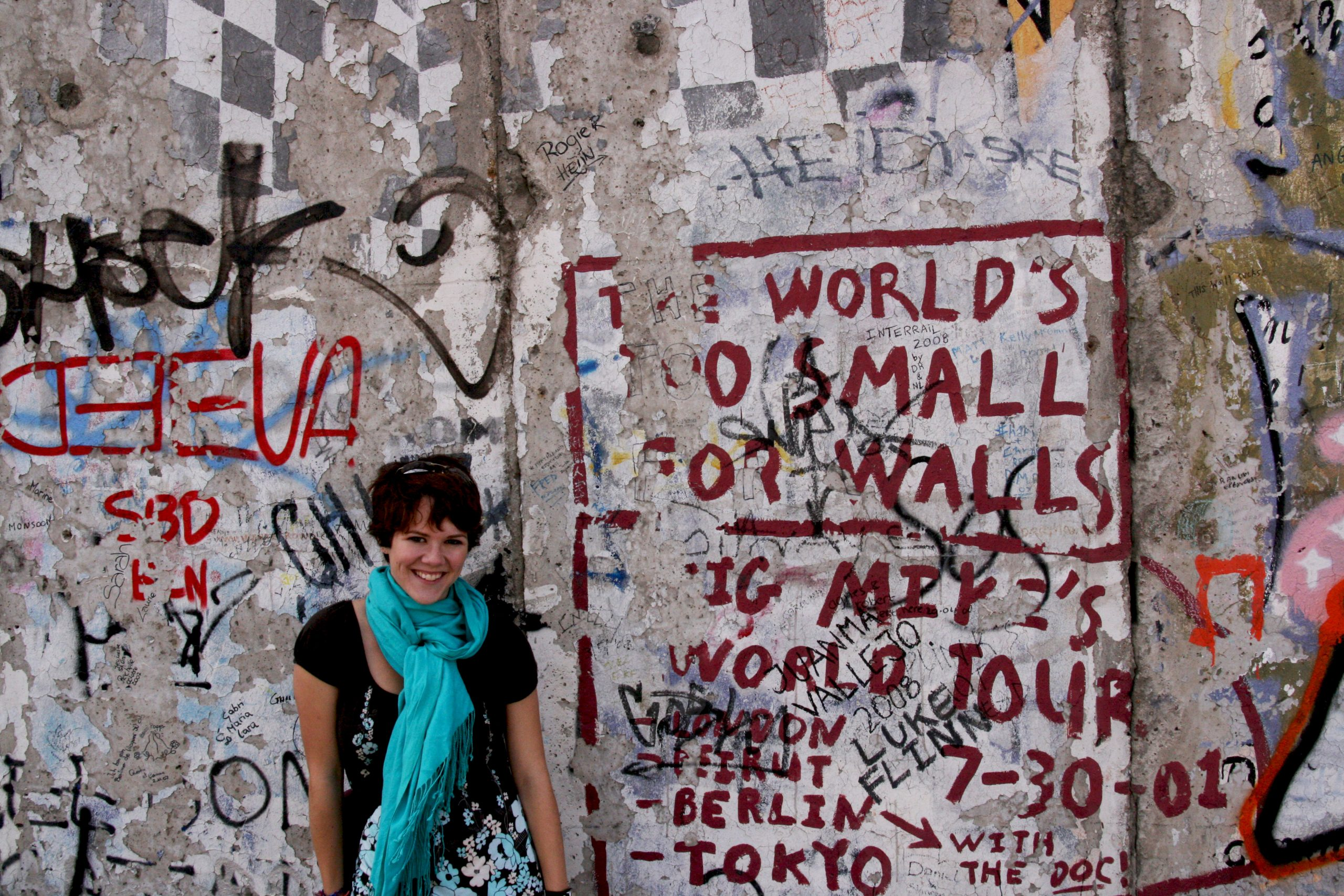 A woman stands in front of the eastside gallery in Berlin. The graffiti on the wall says The World's too small for walls.