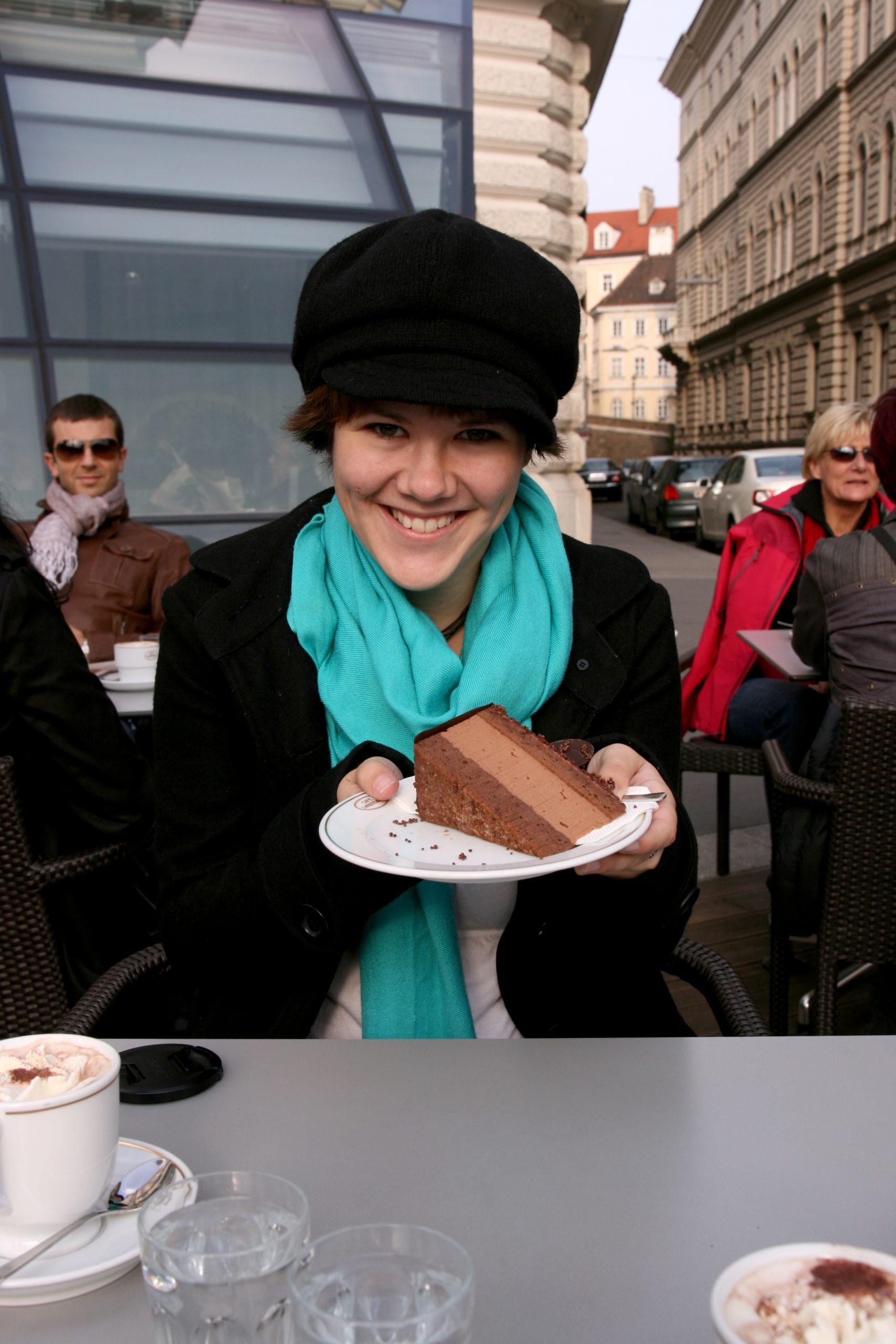 a white woman in a teal scarf and a black hat holding a slice of chocolate cake at an outdoor cafe in Vienna