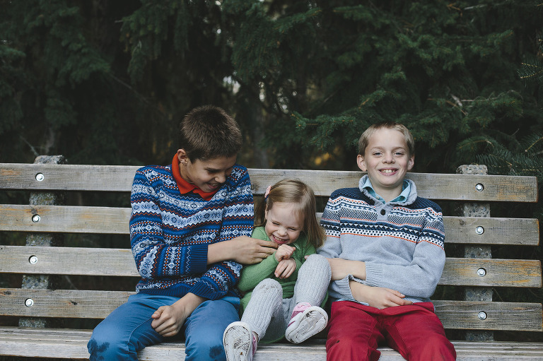 Siblings together candid photos tickling on a bench // Emily Wenzel