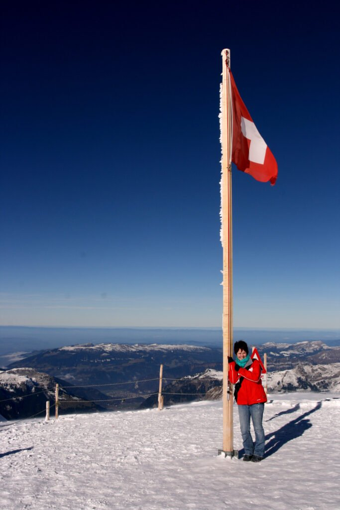 the author standing in front of a swiss flag at the Jungfraujoch in Interlaken in 2008