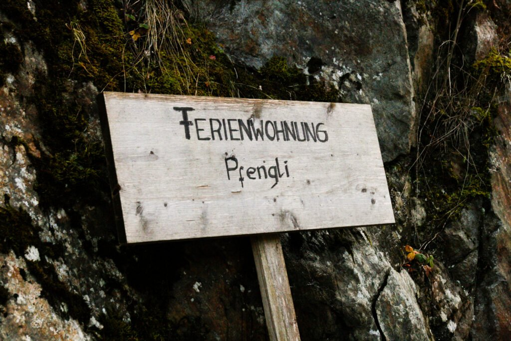 A wood sign with the words  Ferienwohnung Pfengli  on it.