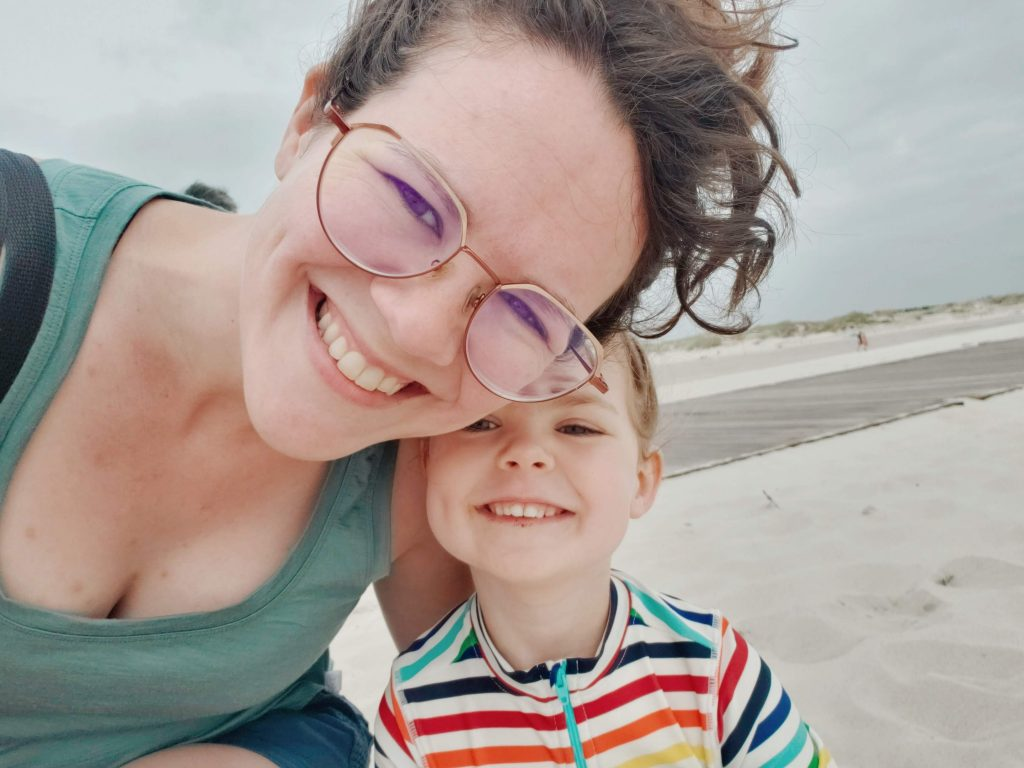 The author and her daughter at the beach. She had dark curly hair and is wearing a blue-green tank, the daughter is blond with rainbow stripes on her top. All around them is white sand.